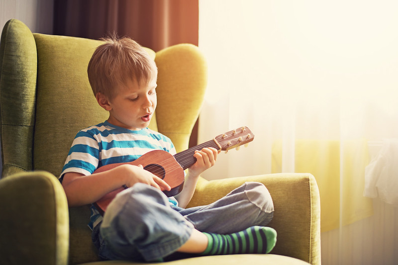 Boy in armchair playing small guitar.