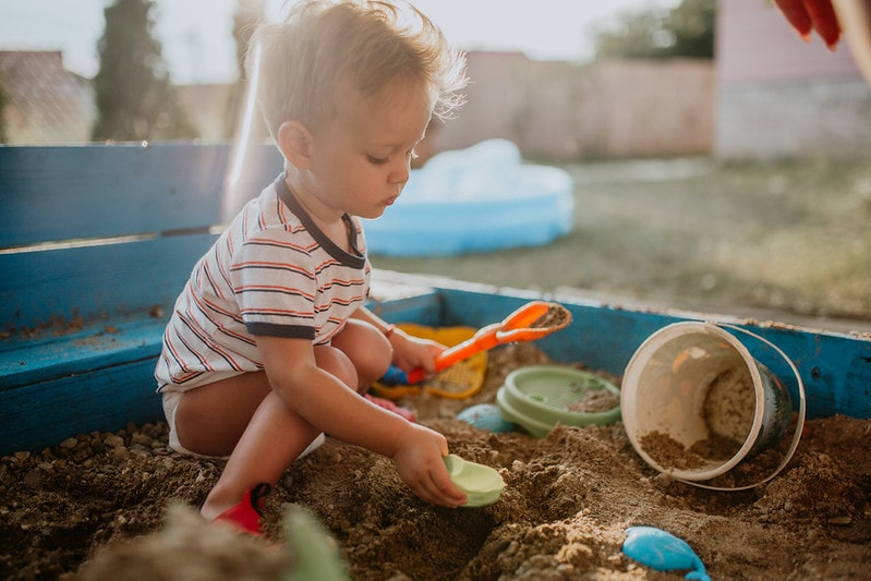 Child playing in sandpit outside having fun.