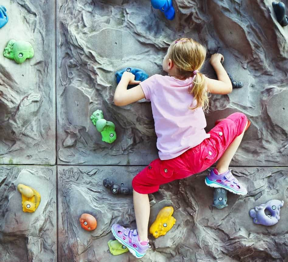 Little girl climbing on the wall with grips for hands and feet.