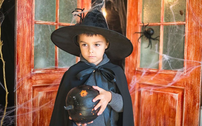 Boy in wizard outfit holding mystic ball.