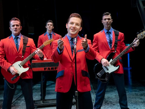 Actors on stage wearing red suits and singing in the show Jersey Boys.