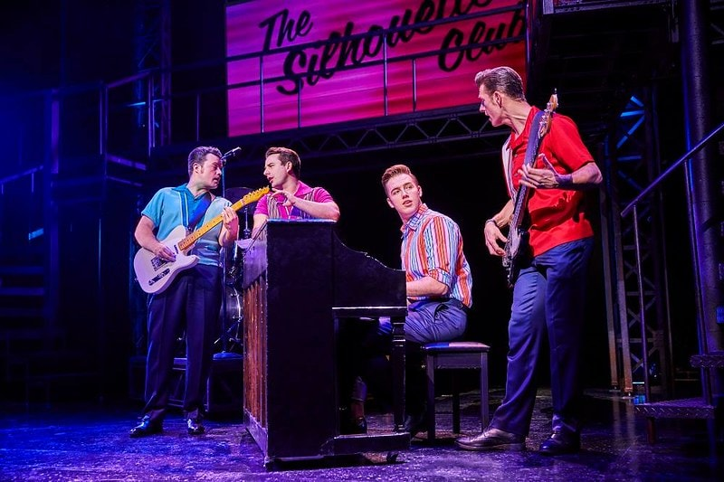 A scene from the show Jersey Boys where the band are rehearsing on the piano and guitars.