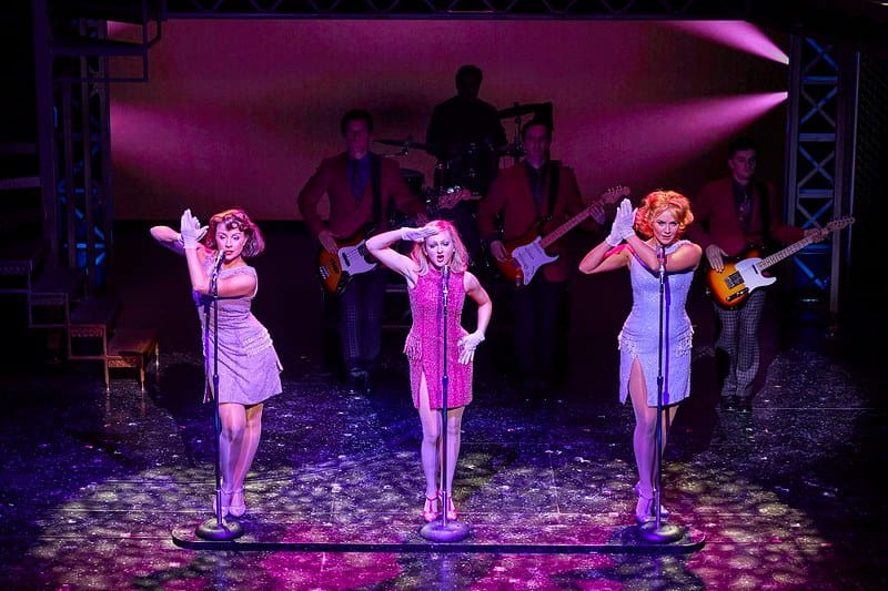 Three female singers on stage singing in the show Jersey Boys.