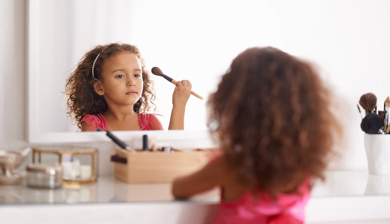 Girl having fun in her bedroom, doing makeup in the mirror on the dressing table.