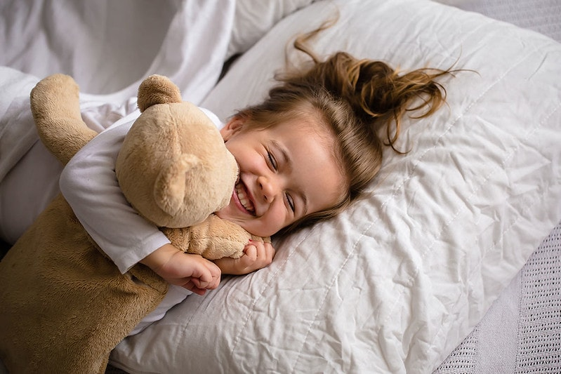 Toddler happily sleeping in bed with cuddly toy.