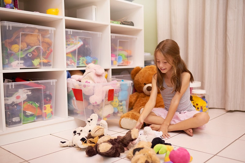 Child with cuddly toys spread out on floor.