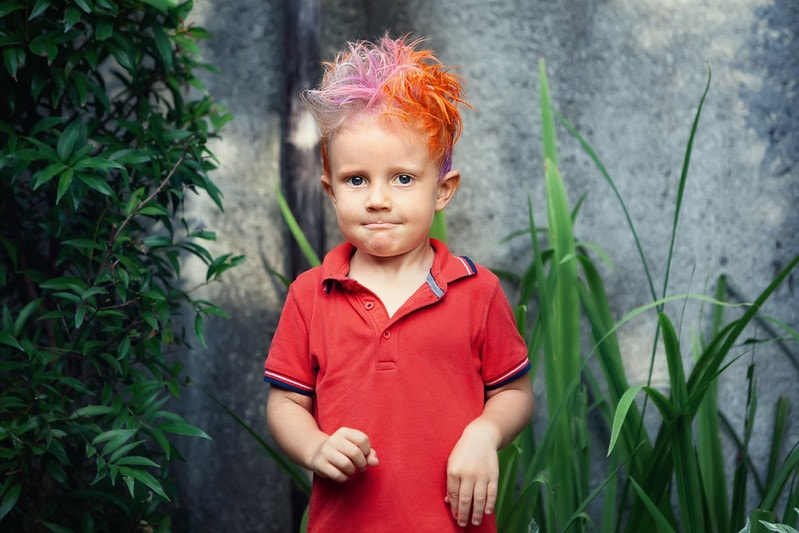 Portrait of young boy with colourful pink and orange hair.