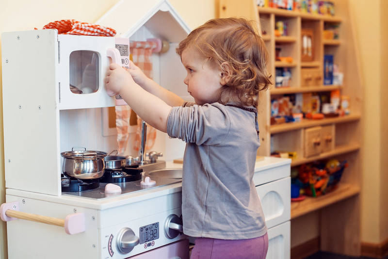Girl having fun using toy washing machine in toy kitchen.