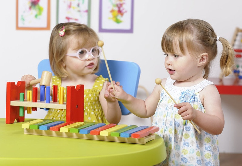 Toddlers playing with musical playset.