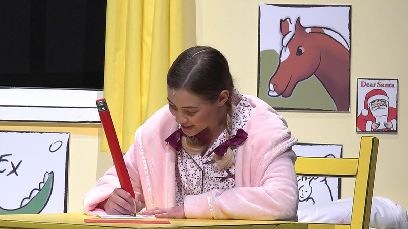 An actress on stage playing a young child writing a letter to Santa in the show Dear Santa.