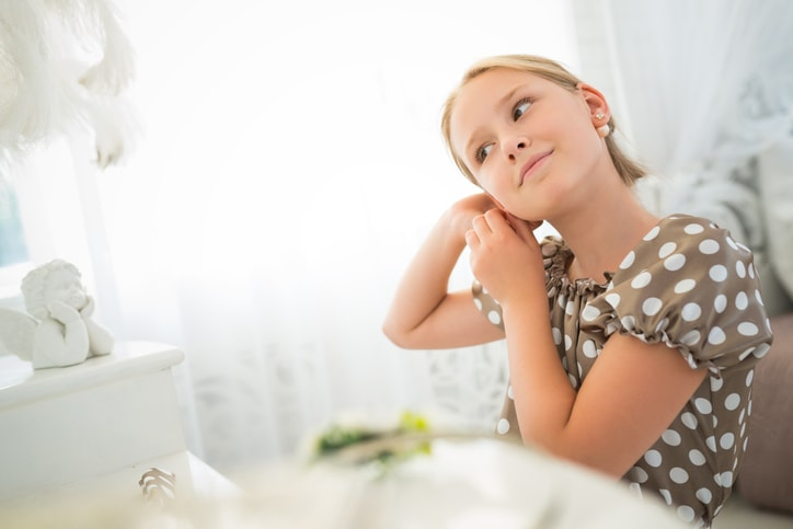 Girl putting special gift earring on.