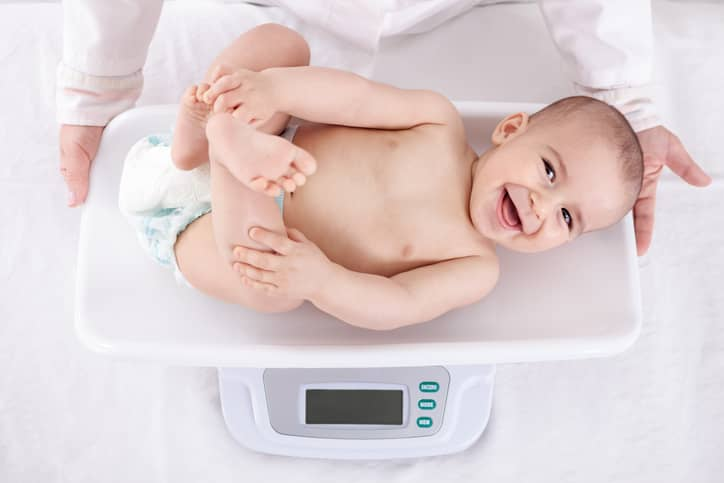 Baby smiling while being weighed.