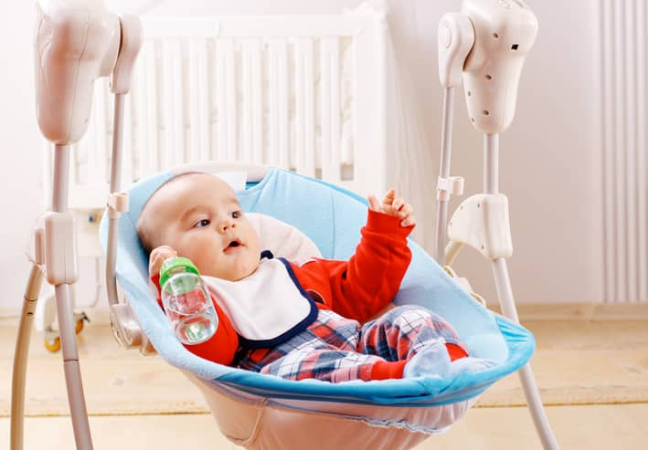 Boy in baby swing with bottle.