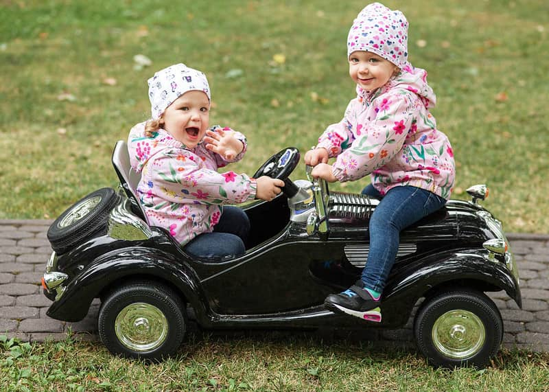 Two girls riding in an electric car.