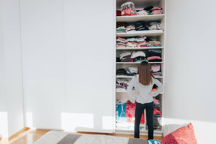 Girl standing in front of wardrobe.