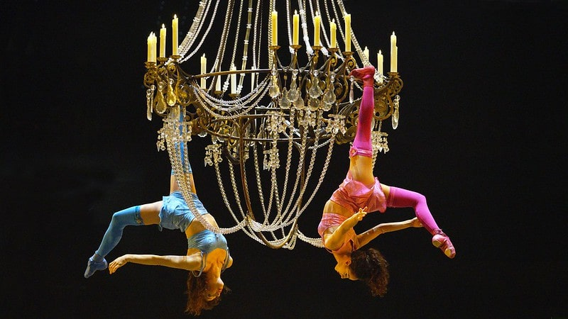 Two acrobats hanging from a large chandelier in the Cirque du Soleil show.
