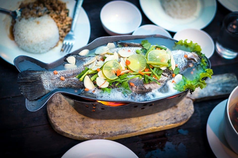 Fish in a plate covered with lemon slices and other vegetables