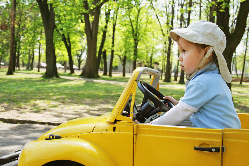 Child in yellow car driving.