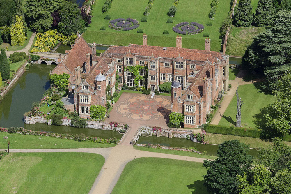Aerial view of the square structure of Kentwell Hall and its moat that runs halfway around it.
