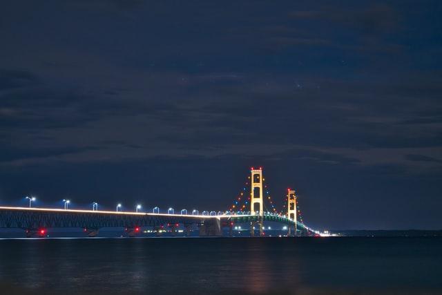 The Mackinac Bridge is lit up at night.