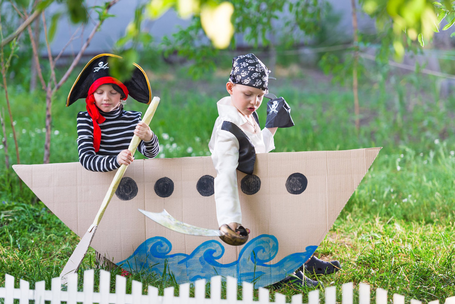Two boys playing in makeshift pirate ship.