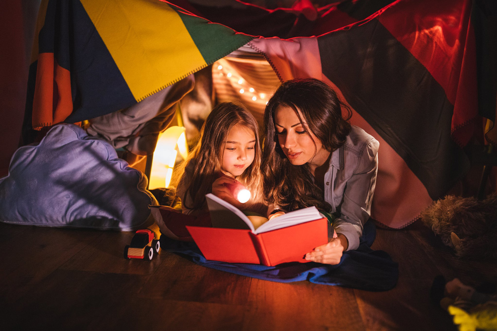 Mother and daughter in bedroom den reading a book together.