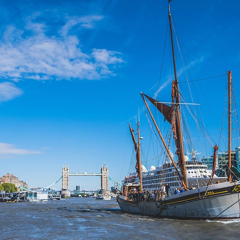A wooden sailing barge on the River Thames with Tower Bridge in the background.