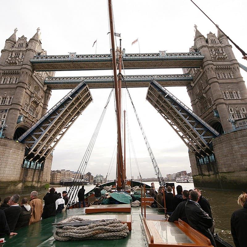 A wooden sailing barge cruising beneath a raised Tower Bridge.