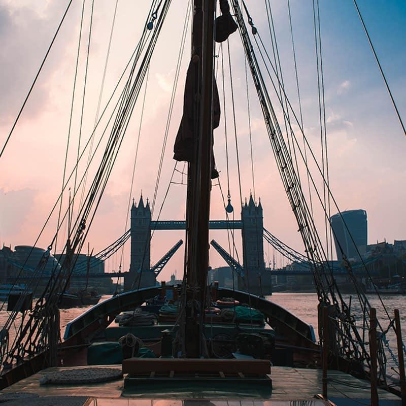A wooden sailing barge at dusk.