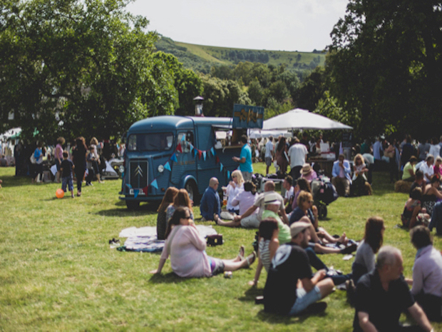 A group of people sitting on the grass at Firle Vintage Fair with vintage VW camper van in the background.