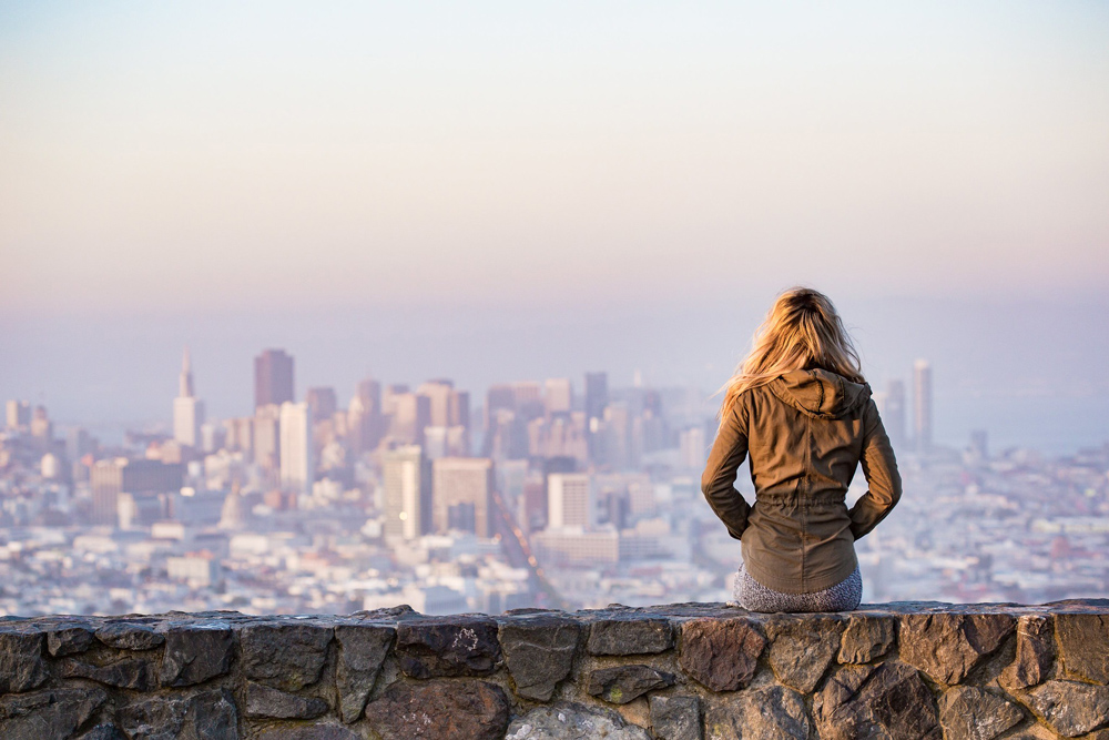 Woman looking out at city skyline.