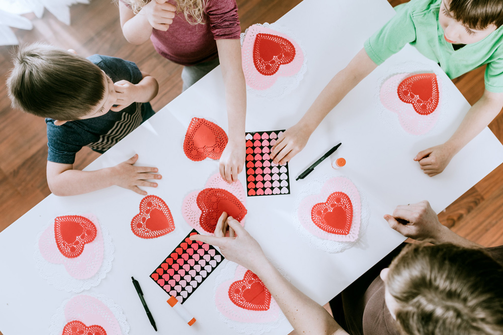 Children making cards with love hearts.