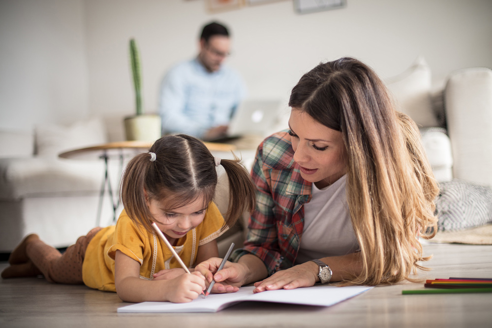 A mother helping her young daughter with an online learning activity.