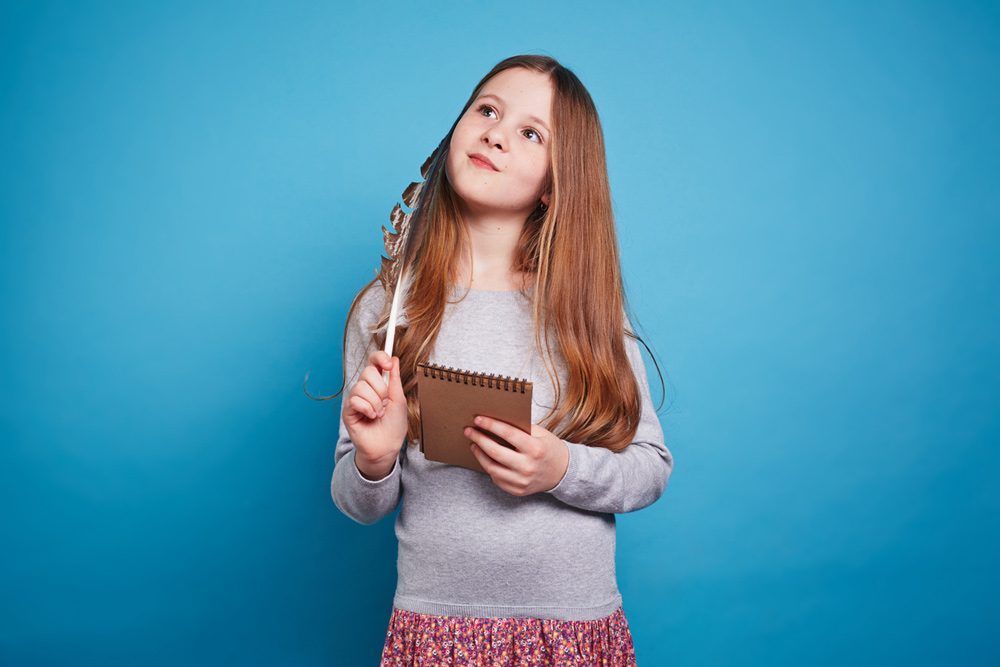 A girl looking thoughtful with her notepad against a blue background.