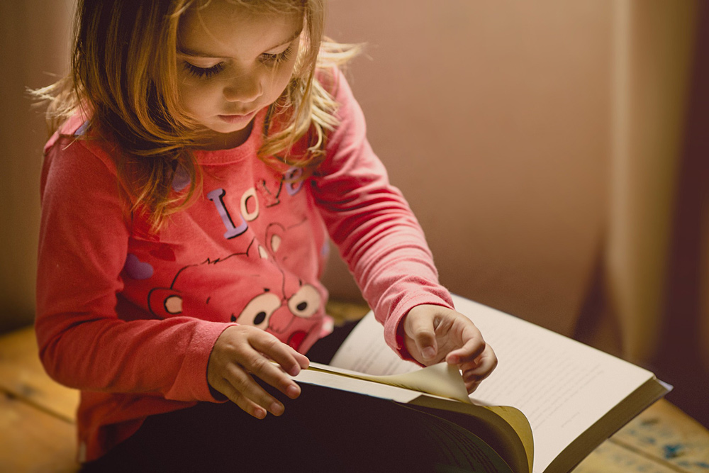 Little girl reading a book.