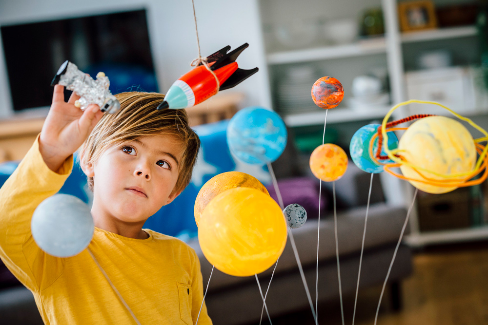 Boy playing with solar system project.