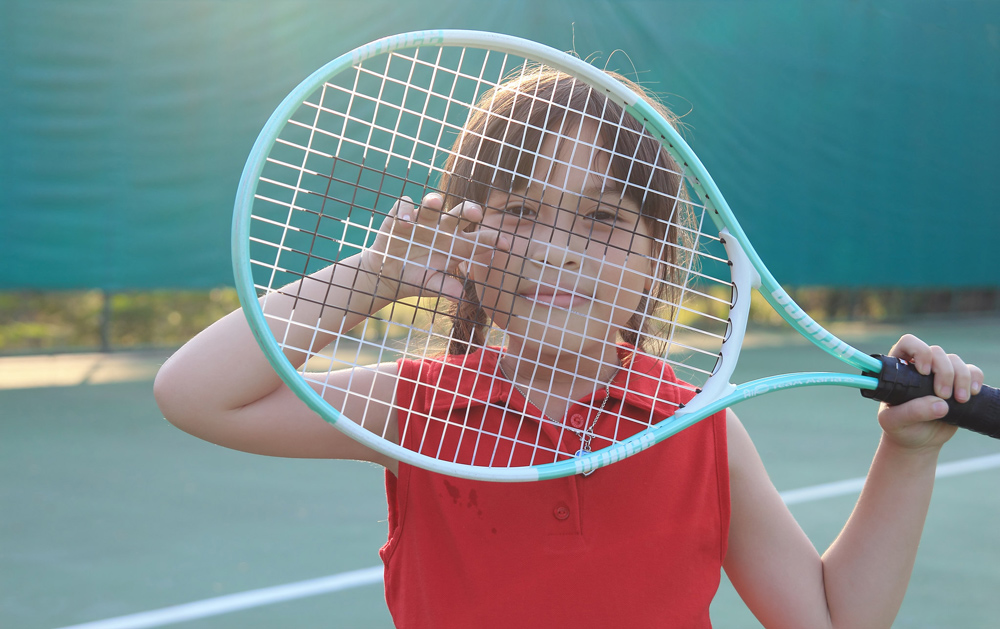 A girl looking through strings on tennis racket.