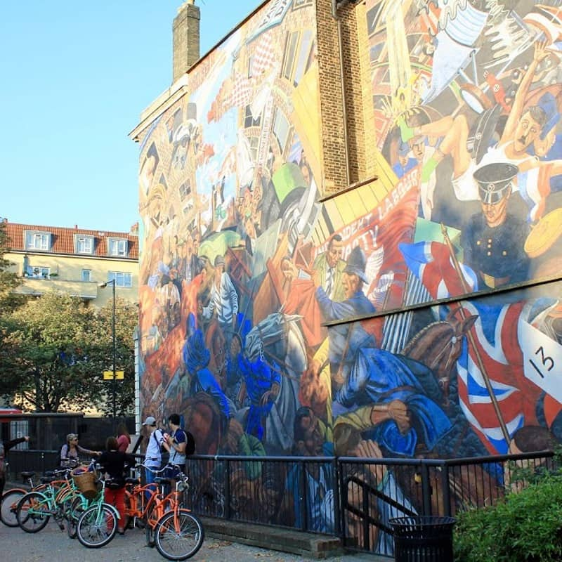 Some bikes next to the mural on Cable Street.