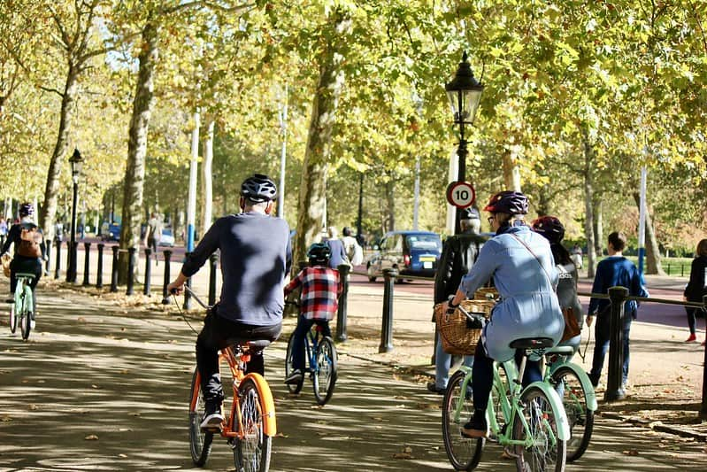 A group of people cycling through a park in London.
