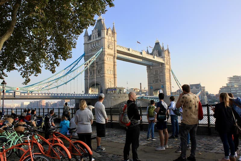 Some cyclists standing by the River Thames looking at Tower Bridge.