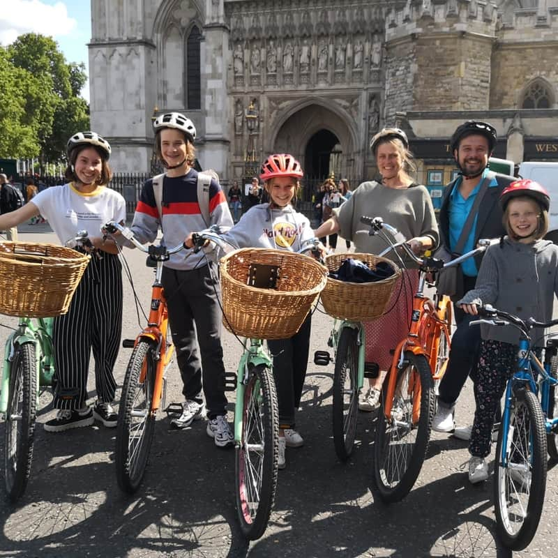 A family standing with their bikes in front of Westminster Abbey.