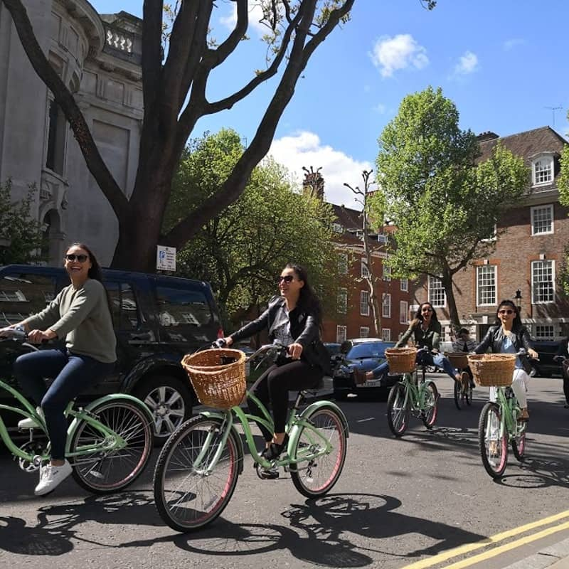 A group of women cycling through London on brightly coloured bikes.