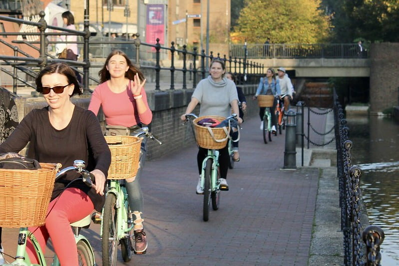 A group of women cycling next to a canal.