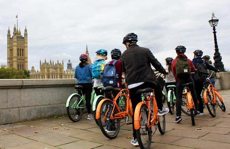 Some cyclists taking a break and looking at the Houses of Parliament.