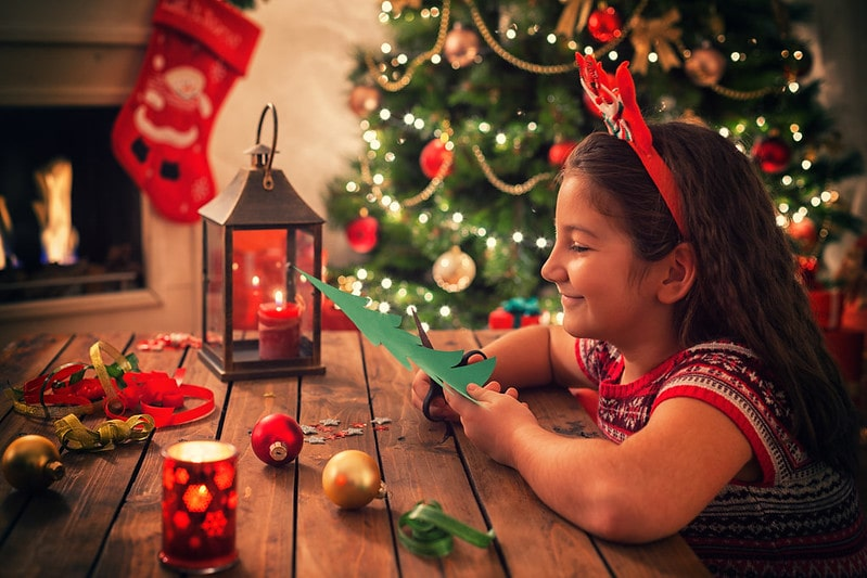 A girl making Christmas decorations at home.