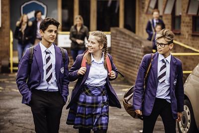 School kids walking and talking wearing a backpack.