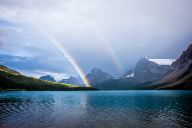 Rainbows and mountains and a lake create beautiful colors combinations.
