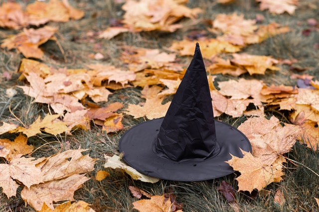 Witches fly on a broomstick and wear a black hat.