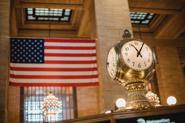 A vintage clock and the American flag.