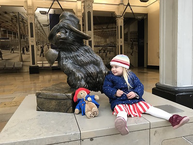 An innocent child sitting alongside Winnie the Pooh's sculpture